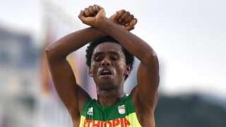 Ethiopian runner makes protest sign as he crosses line in Rio