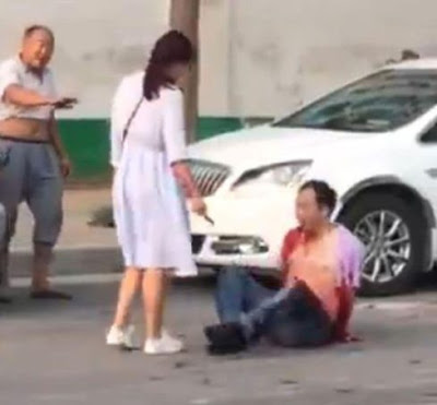 Photos/video: Woman stabs 'cheating husband' with knife in front of passers-by