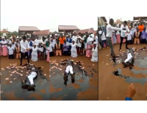 VIDEO: Pastor causes a stir as he rolls in engine oil, while members spray money on him during church crusade