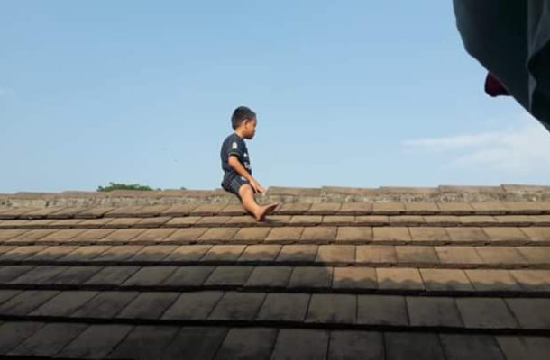 PHOTO: Little boy scared of getting circumcised climbed up a roof ; refuses to come down after 3 hours