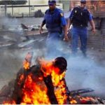 PHOTO: Police Officer seen laughing as a Nigerian burnt alive