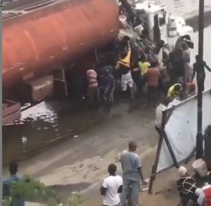 SHOCKING VIDEO: Residents spotted scooping fuel from tanker that spilled its content
