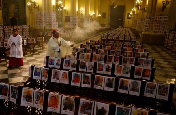 Coronavirus: Powerful image of archbishop in church surrounded by pictures of virus victims
